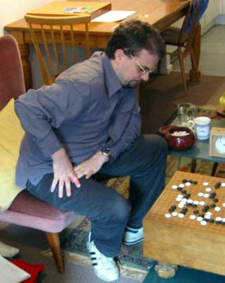 A photograph of Matthew Cocke leaning forward to contemplate his next move